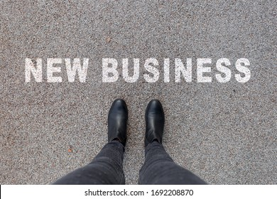 Black shoes standing on the asphalt concrete floor. Text New Business. Feet shoes walking in outdoor. Youth Selphie Modern hipster