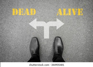black shoes standing on the asphalt concrete floor at the crossroad - dead or alive