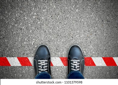 black shoes standing on the red-white line. Breaking the rule. Not allow and prohibited. Limit and end.