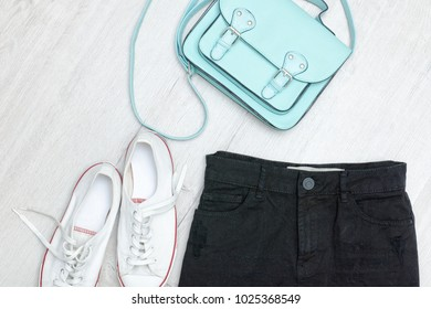 Black shorts and sneakers, mint bag. Fashionable concept. Wooden background.