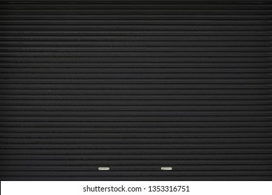 black shutter door with stainless steel holder. grunge black metal foldable door background and texture.