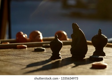 Black side chess piece on a Thai chess board in an evening