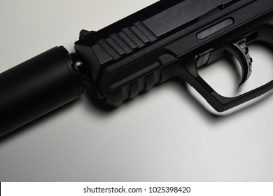 Black Silencer attached to Black 22 caliber pistol