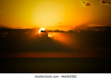 Black silhouette of an airplane on a background of a beautiful sunset over the sea. Toned.