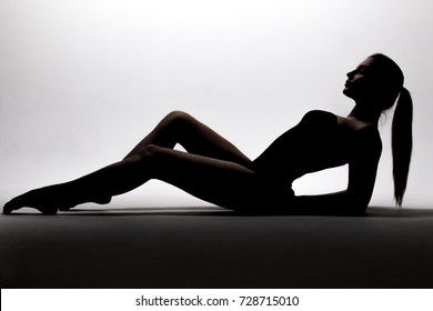 Black silhouette of a beautiful young woman with long hair gathered in bunches lying on the floor on a white background