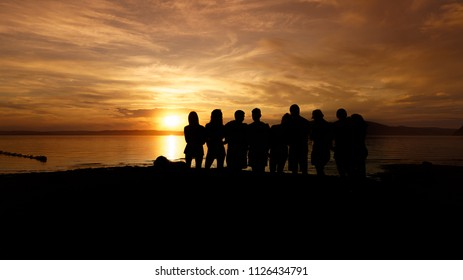 Black silhouette of a crowd of people at sunset