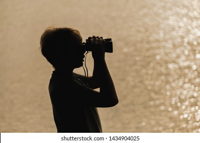 Black silhouette of cute curious kid exploring nature using old vintage binoculars. Boy isolated on golden blurry water of river or sea background. Horizontal color photography.