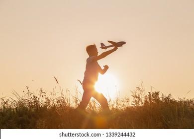 Schwarze Silhouette süßer glücklicher, fröhlicher Kinder, die schnell auf dem grasbewachsenen Hügel auf dem Lande herumlaufen und dabei große Spielzeugflugzeuge in der Hand halten. Junge spielt abends bei Sonnenuntergang. Horizontale Farbfotografie.