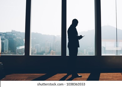 Black silhouette of financial manager standing near big window and downloading file with accounting reports on mobile phone.Male proud ceo reading last business news on smartphone standing in office