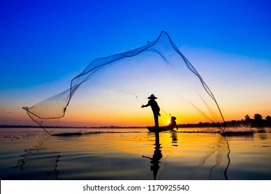 The black silhouette of the fisherman who was prowling the fishing net in the morning of the day when the sun was rising in the reservoir.