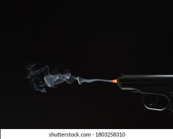 black silhouette of a gun with fire and smoke