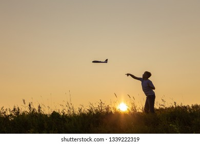Black silhouette of happy caucasian child boy playing with toy airplane outside in meadow on sunny sunset time. Dreaming, imagination, curiosity concept. Horizontal color photography.