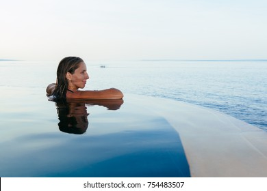 Black silhouette of happy woman on summer beach holiday relaxing in luxury spa hotel in infinity swimming pool with blue sea view.