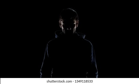 Black silhouette of mysterious man wearing hood, intention to commit crime