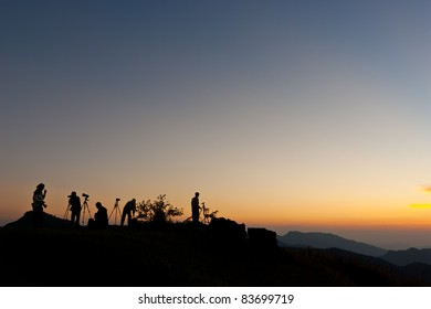 Black silhouette of photographers on mountain after sunset at do