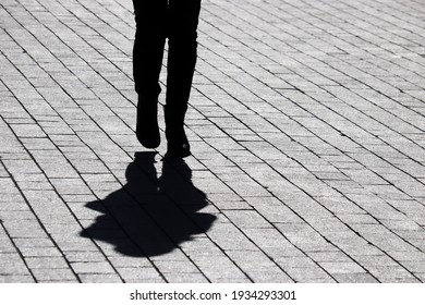 Black silhouette and shadow of lonely woman walking on a street. Concept of loneliness, dramatic human life