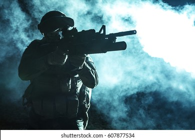Black silhouette of soldier with grenade launcher in the smoke moving in battle operation. Back light, cropped, toned and colorized