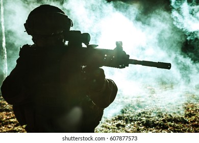 Black silhouette of soldier in the smoke moving in battle operation. Back light, cropped, toned and colorized