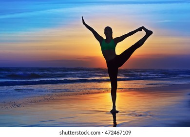 Black silhouette of woman stretching at yoga retreat on sunset sand beach, colorful sky, ocean surf background. Lifestyles, people outdoor activity, sport on family summer vacation on tropical island