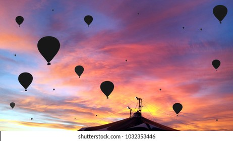 Black silhouettes of the hot air balloons over the circus tent on colorful sunset background