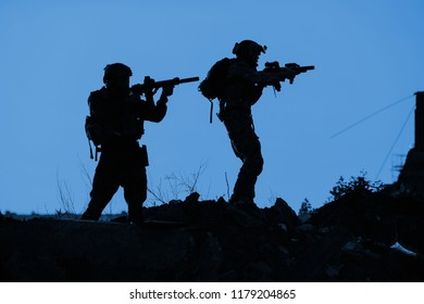 Black silhouettes of pair of soldiers in the battle operation. Military and war concept
