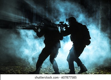 Black silhouettes of pair of soldiers in the smoke moving in battle operation. Back light