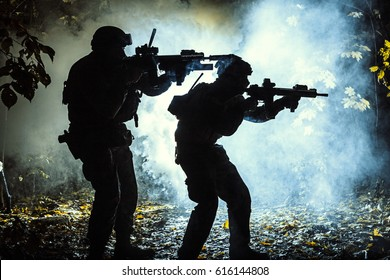 Black silhouettes of pair of soldiers in the smoke haze moving in battle operation. Back light