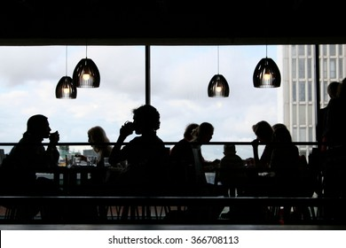 Black silhouettes of people having lunch inside a modern restaurant with big windows