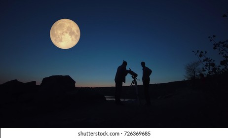 Black silhouettes of people looking through telescope on big red moon in dark twilight on shore.