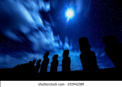 Black silhouettes of standing moais against starry blue sky in Easter Island