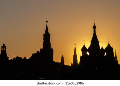 Black silhouettes of the towers of the Moscow Kremlin and St. Basil's Cathedral on the red square. Sunset evening view.
