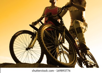 black silhouettes of young adult activity Couple friends in shirt of two bicyclists on brink rock looks at yellow summer sunset sky background in love ride bicycles along beach horizon  No face