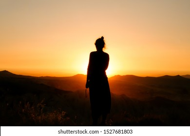 black silhoutte of a woman against a orange red yellow sunset with little mountains on the background. a collorful contrast