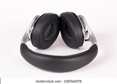 Black silver headphones lays on light background.