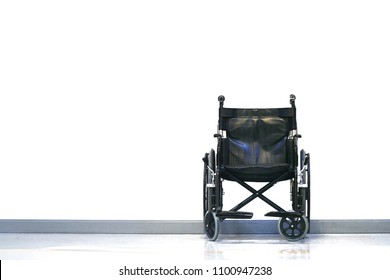Black and silver invalid wheel chair in hospital on white background with light.Health care and Disability people concept.Copy space empty blank for text.