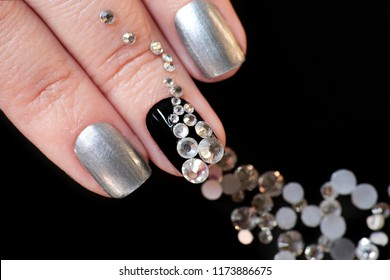 Black silver manicure on short nails with a design of a scattering of rhinestones of different shapes on a black background close-up.Nail art.