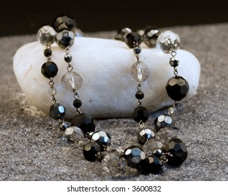 Black and silver necklace on a white stone