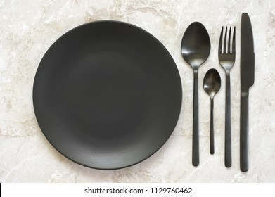 Black silverware and empty plate on marble. Top view point.