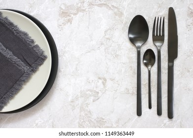 Black silverware and empty plates with napkin on marble. Top view point.