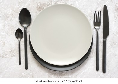 Black silverware and empty plates on marble. Top view point.