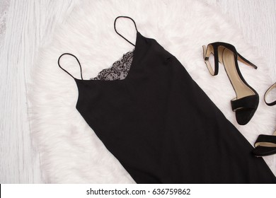 Black simple dress with lace and shoes on white fur, a fashionable concept. Top view