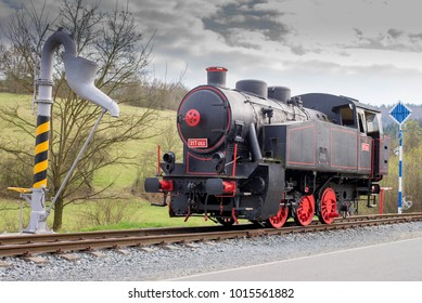Black single steam locomotive with red wheels. Water pump filling.