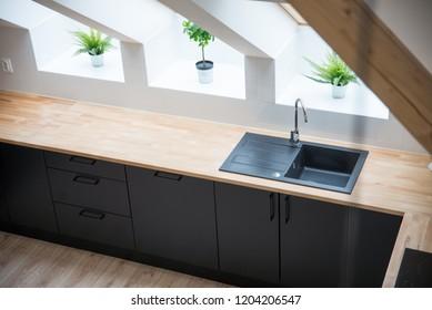 Black sink in the kitchen. Modern kitchen in the attic with black kitchen cabinets