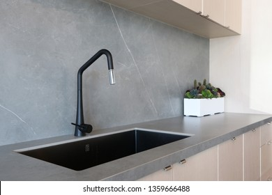 A black sink and a matt-finish black faucet set against a grey countertop and backsplash made of porcelain slabs that mimic the natural look of stones, decorated by green indoor planter.