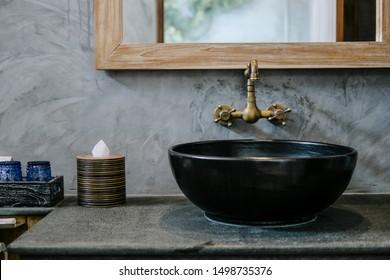 Black sink, vintage copper faucet, gray wall, mirror, loft bathroom interior details. Close up, minimalism concept
