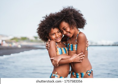 Black sister twins having fun on the beach during summertime - Little female kids laughing and hugging each others - Love and family union concept - Main focus on right chil face