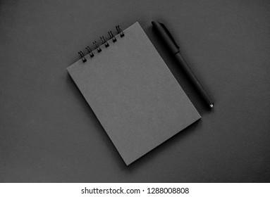 A black sketchpad, a black pen on a black background