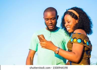 black skin boy and girl using mobile phone laughing while checking something interesting