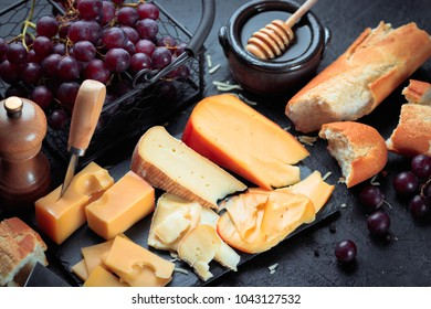 Black slate board with various cheese, decorated with grapes, bread and honey