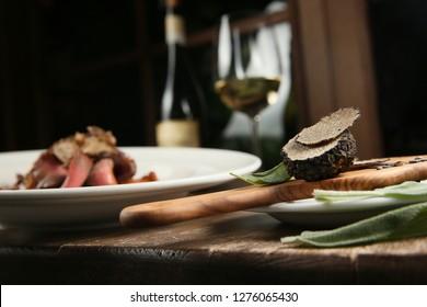 Black sliced truffle mushroom isolated _ closeup _ dark background
